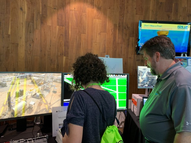 Williams employee and student standing in front of monitors reviewing technology we use to build pipelines.